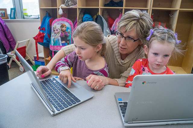teacher helping students use laptops